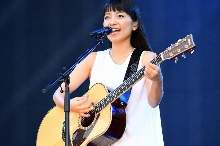 白いシンプルなノースリーブワンピース姿で熱唱する歌手・miwa