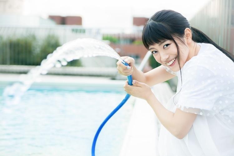 白い半そでのワンピース姿でホースから水を出す歌手・miwa